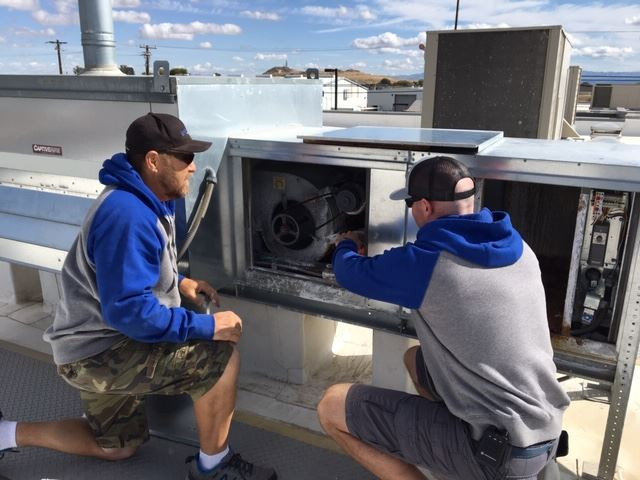 Facilities crew changes air filters on the roof of a county building