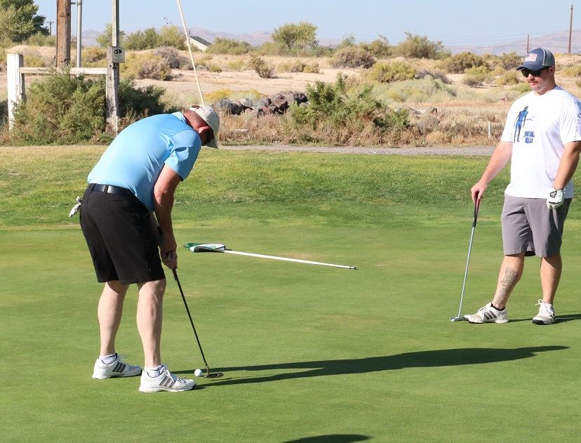 Regan golf tournament player lines up for a putt