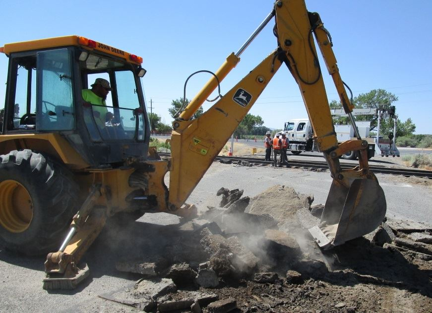 Heavy equipment breaks up road asphalt