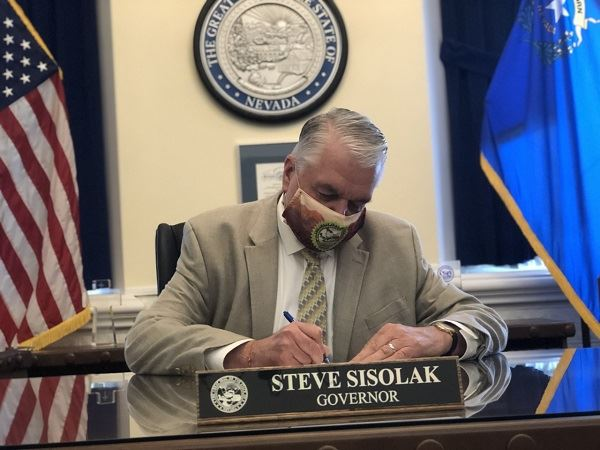 Governor Sisolak masked and signing a document