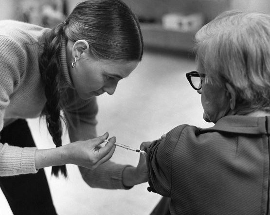 Elderly female receiving a vaccination by a public health clinician